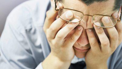 man holding head stressed
