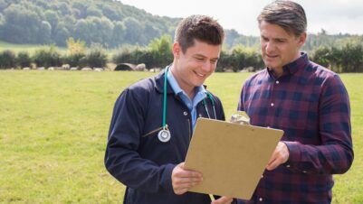 farmer and vet looking at clipboard